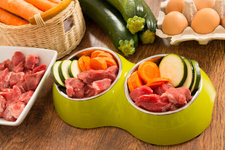 raw: Natural, organic dogs food in a bowl with ingredients zucchini, carrot and raw meat