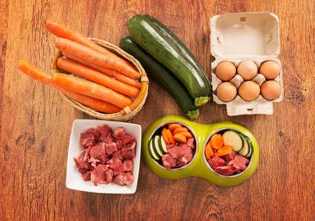 El alimento natural, de perro orgánico en un bol con los ingredientes calabacín, zanahoria, huevos y carne cruda Foto de archivo