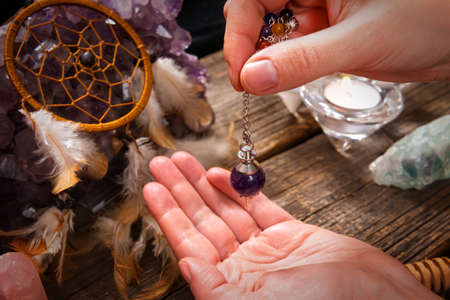 psychic reading: Palm reading, characterization and foretelling the future through the study of the palm with pendulum Stock Photo