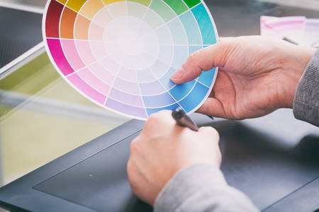stylus pen: Designer using graphics tablet and holdnig color wheel in the office
