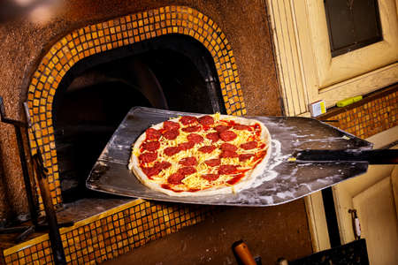 pizza dough: Fresh original Italian pizza on a shovel is putting into a traditional wood-fired stone oven.