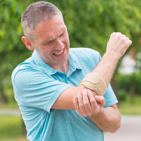 痛みを軽減する肘装具を身に着けている男 写真素材
