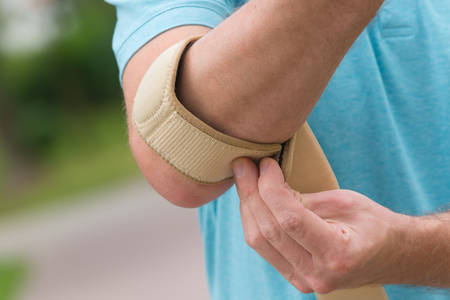 human's elbow: Man wearing elbow brace to reduce pain