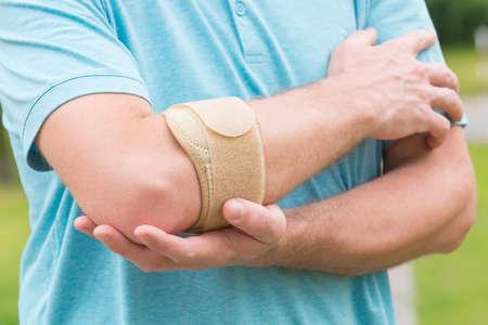 Man trägt Ellenbogenbandage zur Verringerung der Schmerzen Standard-Bild