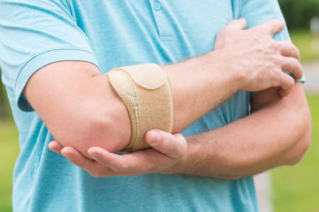 hand pain: Man wearing elbow brace to reduce pain