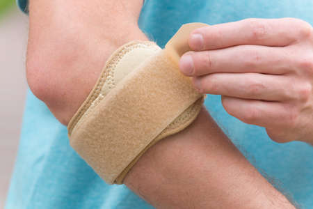stiffness: Man wearing elbow brace to reduce pain