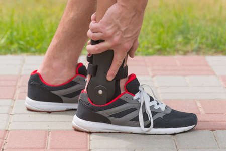 immobilize: Man in athletic sneakers wearing ankle orthosis or brace