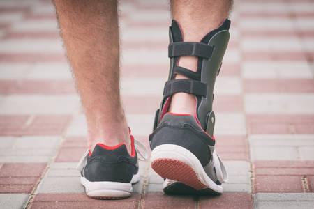 Hombre en zapatillas de atletismo que lleva ortesis de tobillo o un aparato ortopédico Foto de archivo - 59119931