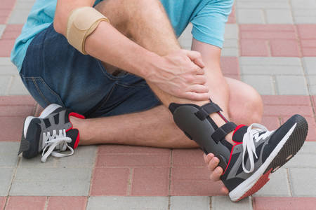Man in athletic sneakers sitting on the street and checking his ankle orthosis or brace