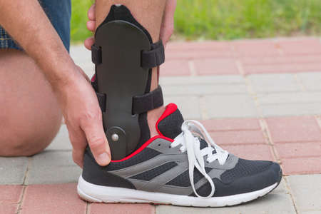 immobilize: Man in athletic sneakers checking his ankle orthosis or brace on the street