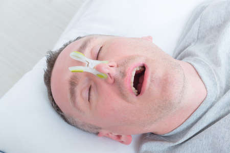 snoring: Snoring man in bed with cloth clip on his nose