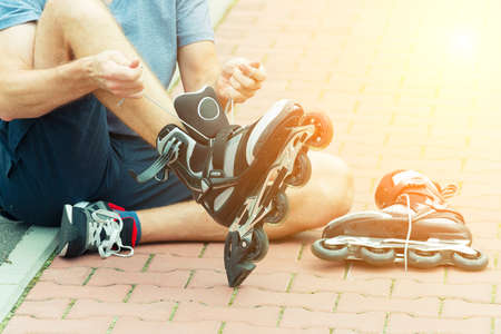 blading: Man preparing for roller blading, putting on rollerblades. Stock Photo
