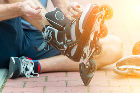 Man preparing for roller blading, putting on rollerblades. Stock Photo