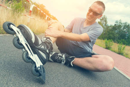 blader: Injured skater sitting and holding his painful leg Stock Photo