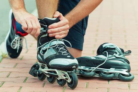 rollerblades: Man preparing for roller blading, putting on rollerblades. Stock Photo
