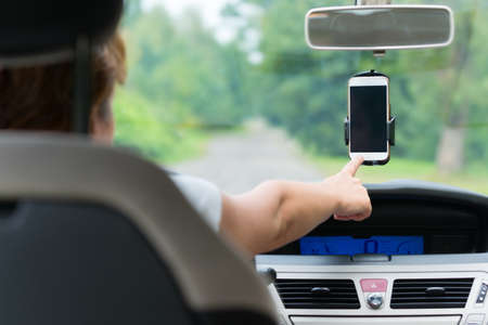 Hand touching screen on smart phone in the car holder to change naigation options or write SMS