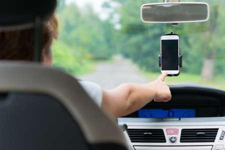 Schermo commovente della mano sul telefono intelligente nel supporto per auto per cambiare le opzioni naigation o scrivere SMS Archivio Fotografico - 65646559