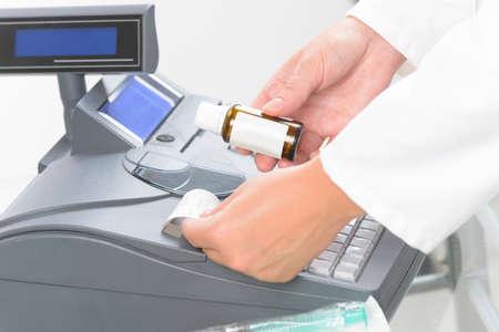 pagando: pharmacist holdnig bottle of medicine and using cash register at pharmacy