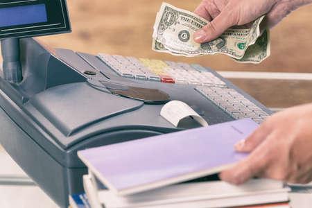 cash money: Vendedor usando caja registradora en la librería y la tenencia de dinero