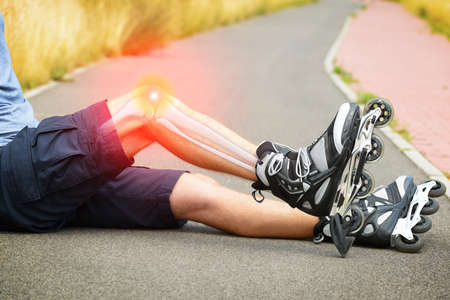 blader: Injured skater sitting with his painful leg Stock Photo