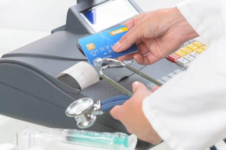 pagando: farmacéutico o médico estetoscopio holdnig y el uso de la caja registradora y tarjeta de crédito en la farmacia o cirugía Foto de archivo