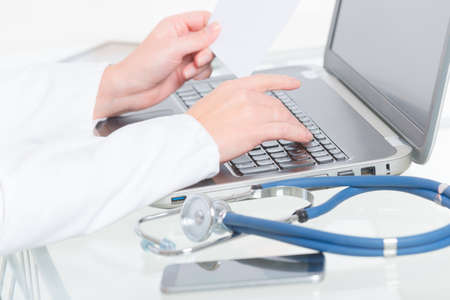 Close up of doctors hands typing on a laptop with stethoscope in the foreground