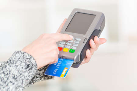 terminals: Entering PIN code on wireless payment terminal with inserted redit or debit card