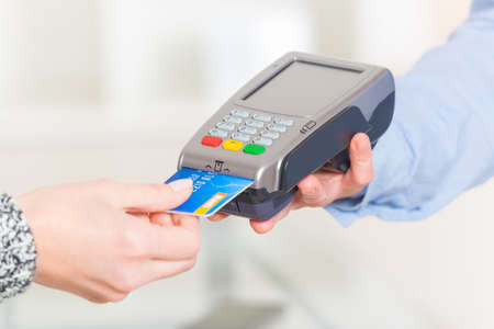 terminals: Paying with credit or debit card in wireless payment terminal at shop Stock Photo