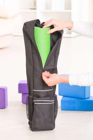 Putting a yoga mat inside a special yoga bag