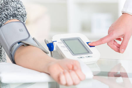 PULSE: Doctor cardiologist measuring blood pressure of female patient in hospital office appointment