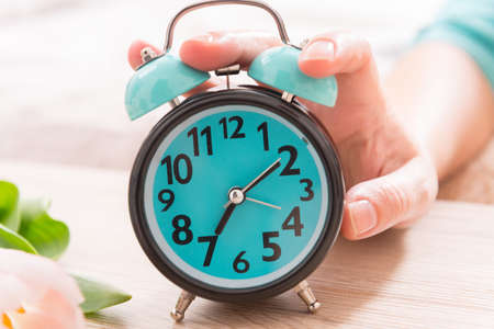 oversleep: Hand on alarm clock trying to turn it off Stock Photo