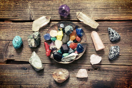 Multiple semi precious gemstones on wooden boardfluorite, quartz, obsidian, rose quartz and many other