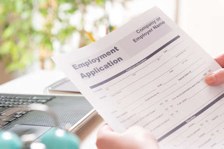 Blank employment application form in hands on a desk