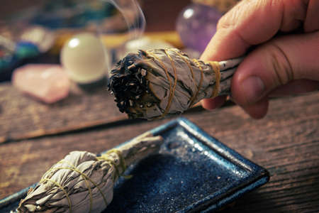 Man's hand with burning natural white sage incense Stockfoto