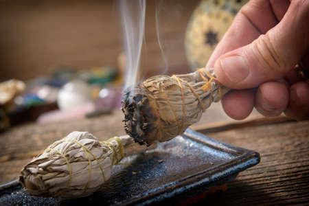 Man's hand met brandende natuurlijke witte salie wierook