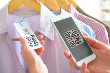 Vrouw scannen QR code van een label in een winkel met mobiele telefoon