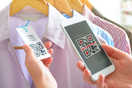Woman scanning code QR d'une étiquette dans un magasin avec téléphone mobile Banque d'images - 74492748