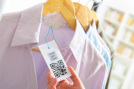 Womans hand with a cloth label with QR code  in a shop
