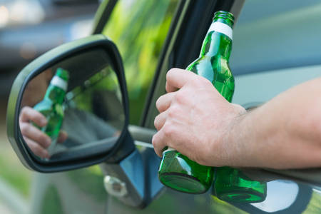 Man holding green bottle of beer in hand while driving a car. Dont drink and drive concept