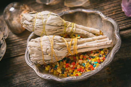 healer: White sage and colorful incense on wooden board