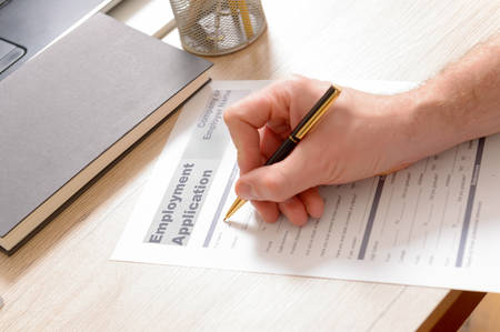 Filling in blank employment application form in hands on a desk