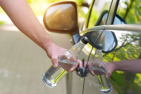 Man opening his car while holding a bottle of alcohol. Dont drink and drive concept
