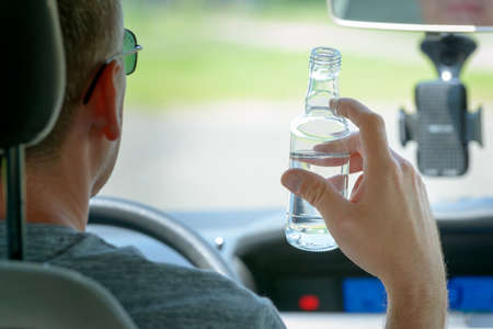 Man driving a car with a bottle of alcohol drink. Don't drink and drive concept photo