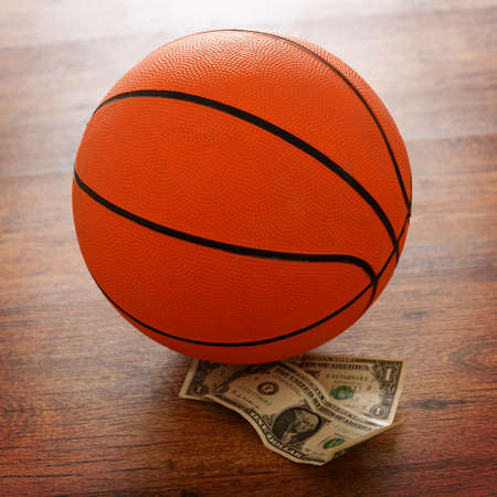 Basketball bet conceptual photo with money and ball on a wooden floor Stock Photo