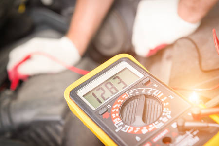 Car mechanic uses a multimeter to check car battery voltage