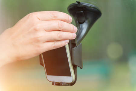 Hand inserting smart phone into the car holder and adjusting clamps Stock Photo
