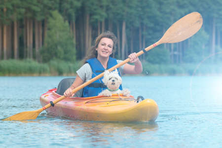 Beautiful woman and her dog on a kayak Stock Photo