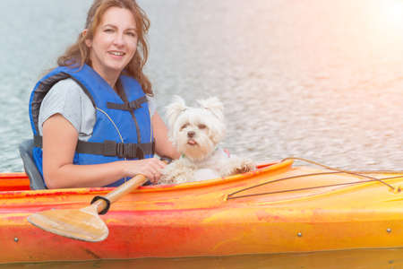 Beautiful woman and her dog on a kayak photo