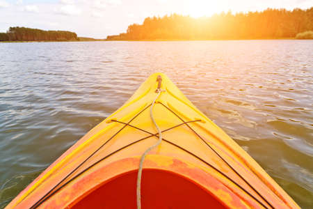 Orange kayak on the water, sun in background Stock Photo
