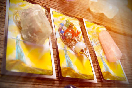 Tarot cards, dowsing tool and crystals on a wooden board Stockfoto